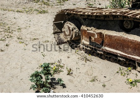 Bulldozer tracks on sand with plants - stock photo