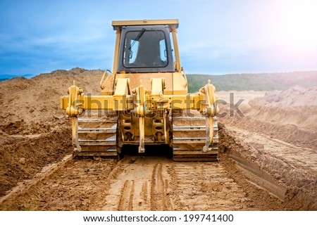 Bulldozer with steel blade moving soil and sand around and working in a sandpit on construction site of a house, road or industrial hall - stock photo
