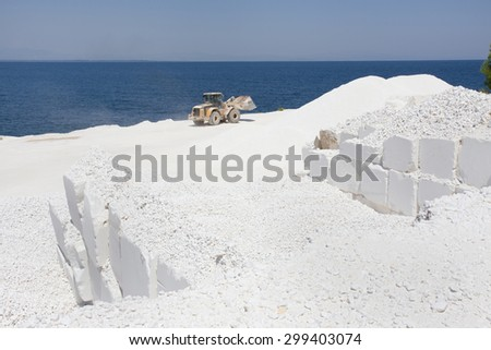 Bulldozer working at white marble quarry on Thassos in Greece, horizon at blue sea in background - stock photo