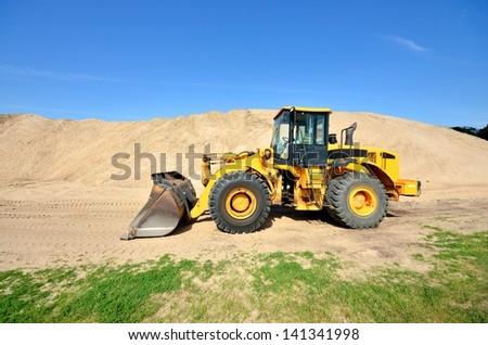 bulldozer working in sand dunes - stock photo