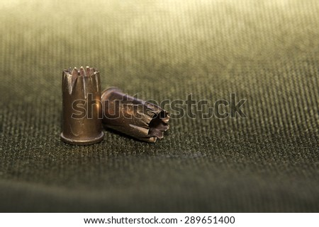 Bullet casings on green textile with selective focus and unusual lighting. - stock photo
