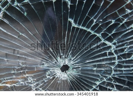 Bullet hole in a shattered piece of glass - stock photo