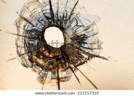 Bullet hole in a window - stock photo