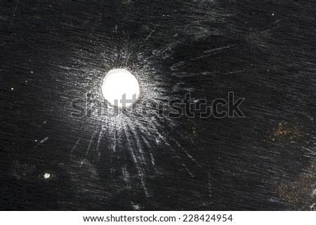 Bullet hole in thick sheet metal from the front view - stock photo