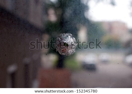 Bullet hole on the dirty glass background. - stock photo