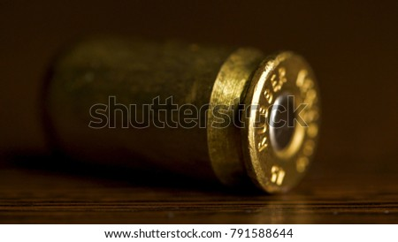 bullet macro with limited dof on a black background, 9mm full metal jacket. Bullet isolated on black background with reflexion. close up gun bullets. Weapon Cartridge case sleeve background texture