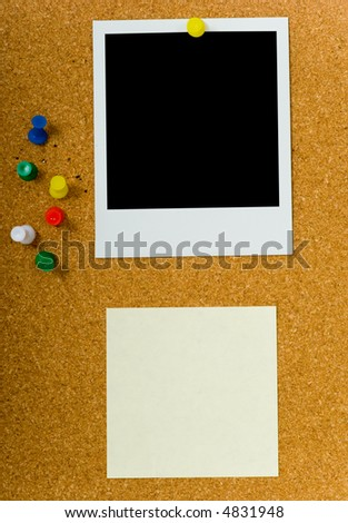 bulletin board with blank  instant photograph and a yellow sticky or post-it note and extra push pins - stock photo