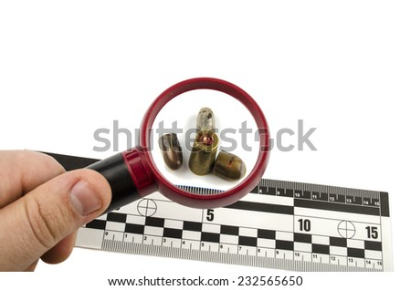 bullets and shell under a magnifying glass with a line of forensic - stock photo