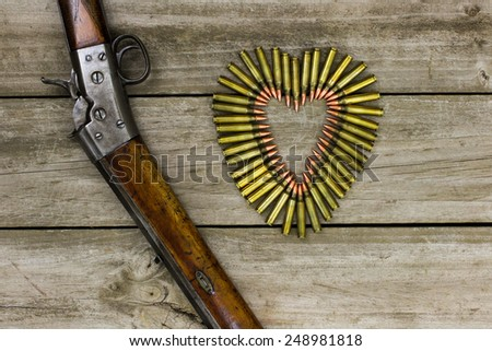Bullets in the shape of heart next to rifle on rustic wooden background - stock photo