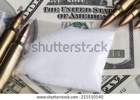 Bullets on dollar banknotes with a bag of white drug powder - stock photo