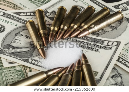bullets on dollar banknotes with white drug powder - stock photo