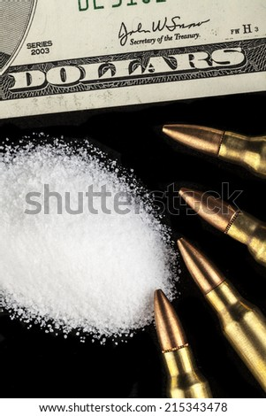 bullets with dollar banknotes with white drug powder on black background - stock photo