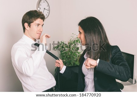Bully Businesswoman Holding Colleague's Necktie - stock photo