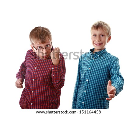 Bullying concept. Two cute schoolboys in colorful shirts showing signs of aggression and welcome (isolated on white background) - stock photo