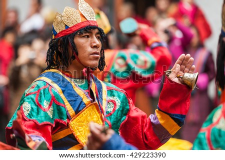 Bumthang, Bhutan, 06 Nov 2011: Performer dancing at festival at Jakar Dzong while holding ceremonial hand bell. - stock photo