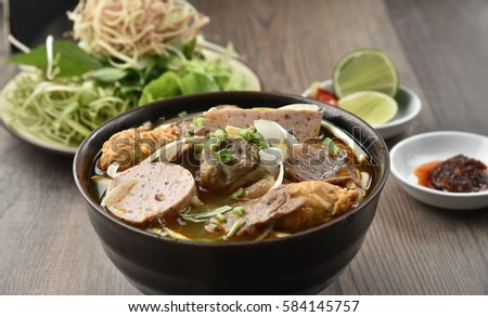 Bun bo Hue - Hue Noodles (Noodles cooked with beef, cooked pork roll, pork meat and eat along with bean sprout, vegetable, banana branch...)
