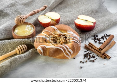 Bun with apple and cinnamon on white wooden board