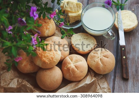 Bun with butter and milk. Breakfast in rustic style. Selective focus - stock photo