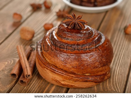 Bun with cinnamon on a brown background - stock photo