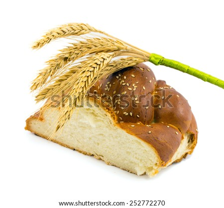 bun with sesame seeds and a bunch of ears of wheat isolated on a white background - stock photo