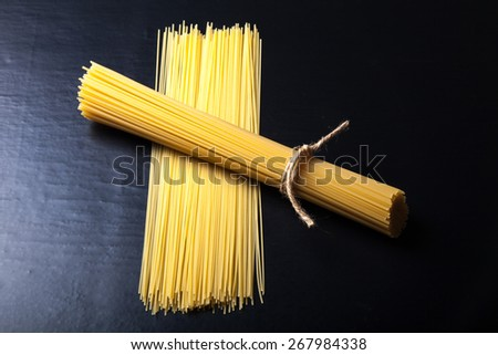 Bunch and pile of pasta spaghetti on a black background. - stock photo