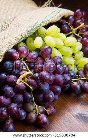 bunch black and green grapes on wooden background - stock photo