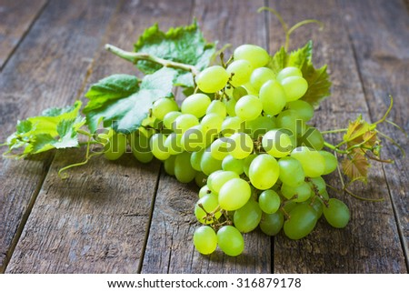 bunch green grapes on wooden background, food closeup