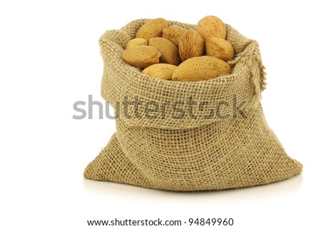 bunch of almond nuts in a burlap bag on a white background
