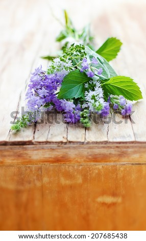 Bunch of aromatic herbs on the vintage wooden cupboard: lavender, mint, thyme, sage - stock photo