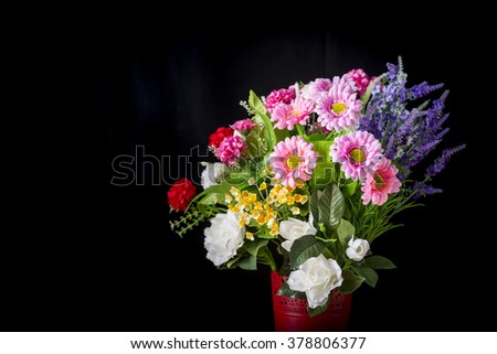 Bunch of artificial flowers on black background