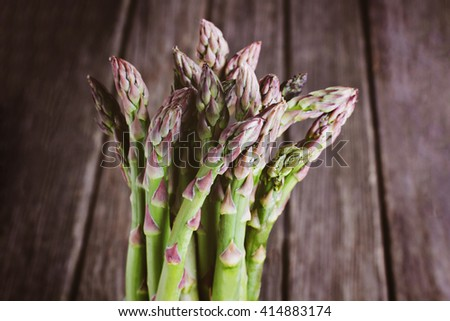 Bunch of asparagus against wooden background - stock photo
