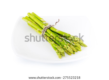 Bunch of asparagus on plate isolated on white - stock photo