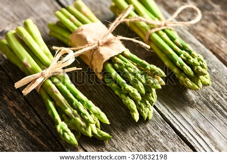 Bunch of asparagus over rustic wooden background - stock photo