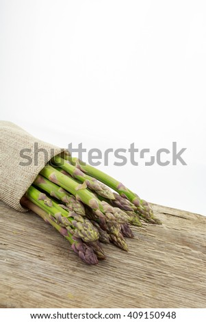 Bunch of asparagus tied with raffia cloth on wooden surface with copy-space, on white background. - stock photo