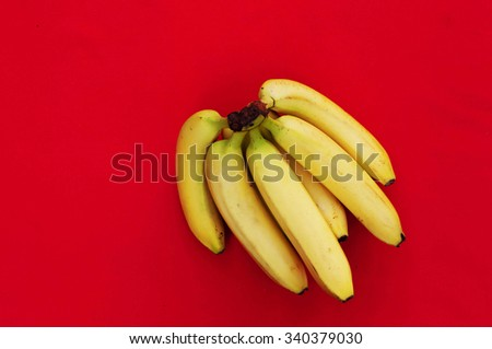 Bunch of bananas on red  background. Fresh organic Banana. Fresh bananas on  red kitchen table. Banan isolated on red.  Fresh fruits. Organic Banana. Sweet. Fruit. Food. With space for text. Top view. - stock photo