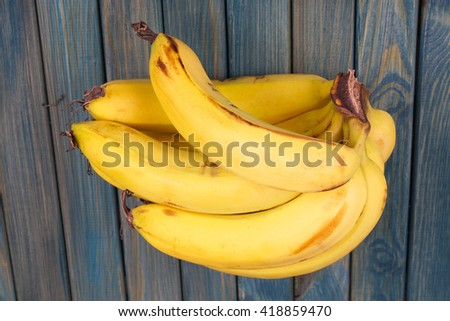 Bunch of bananas on rustic wooden table - stock photo