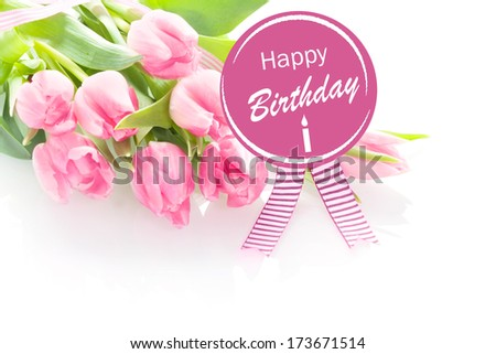 Bunch of beautiful fresh pink tulips with a Happy Birthday greeting message on a round purple rosette with festive ribbons over a white background - stock photo