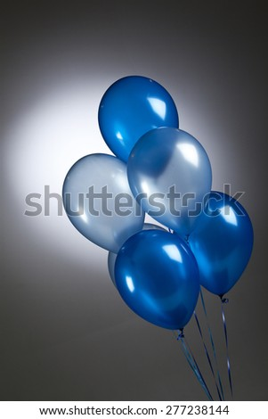 Bunch of blue balloons on a grey background