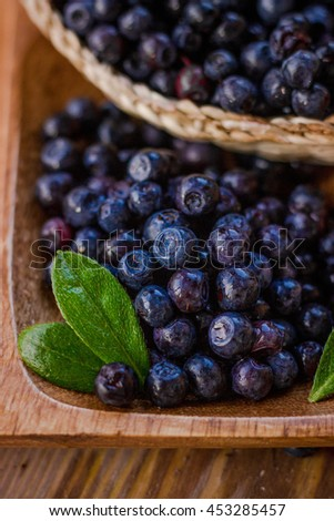 Bunch of blueberries and leaves macro close up. Berries laying in eco wooden plate and basket. Selective focus.