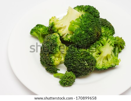 Bunch of boiled green broccoli on plate. - stock photo