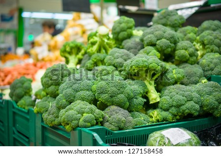 Bunch of broccoli cabbages on boxes in supermarket - stock photo