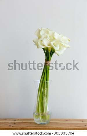 Bunch of callas in the vase on white background