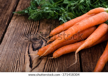 Bunch of Carrots (close-up shot) on an old, wooden table - stock photo