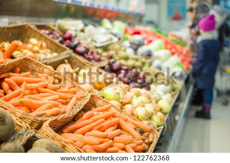 Bunch of carrots, onions, cabbages, peppers and tomatoes on shelves in supermarket - stock photo