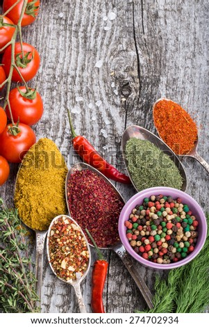 Bunch of cherry tomatoes, herbs, small bowl and antic metal spoons with different kinds of spices, sea salt and red hot chili peppers on old wooden board. Selective focus. - stock photo