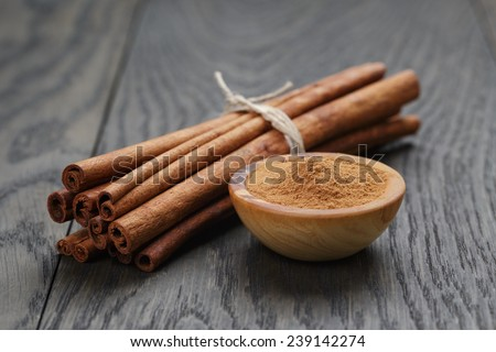 bunch of cinnamon sticks tied with twine and powder in bowl, on rustic oak table - stock photo