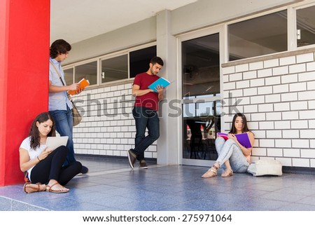 Bunch of college students waiting in the hallway outside a classroom and studying before a test