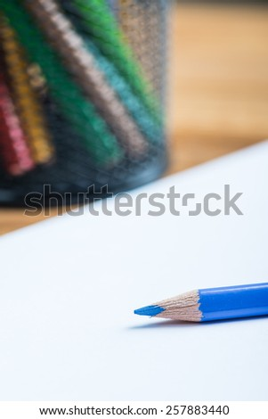 Bunch of color pencils with a white paper sheet