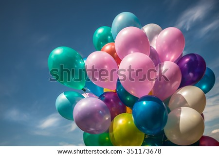 Bunch of colorful balloons on a blue sky background - stock photo