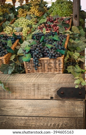 Bunch of Colorful Grapes in Wicker Basket on Wooden Shelf For Sale